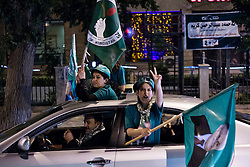 © Licensed to London News Pictures. 27/04/2014. Sulaimaniya, Iraq. Supporters of the Patriotic Union of Kurdistan (PUK) political party flash victory signs and hold flags bearing the party logo and a picture of Jalal Talabani, leader of the PUK, during celebrations in the lead up to the 2014 Iraqi parliamentary elections in Sulaimaniya, Iraqi-Kurdistan.<br /> <br /> Although banned in other parts of Iraqi-Kurdistan, the days leading up to an election in Sulaimaniya sees political supporters of all the three main parties parading up and down the main street of the city, waving flags, honking horns, letting off fireworks and firing pistols and rifles into the air.<br /> <br /> The period leading up to the elections, the fourth held since the 2003 coalition forces invasion, has already seen six polling stations in central Iraq hit by suicide bombers causing at least 27 deaths. Photo credit: Matt Cetti-Roberts/LNP