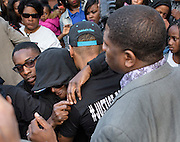 Baltimore, Maryland - April 21, 2015: Freddie Gray's mother, with a hood over her head, middle, surrounded by family members and supporters, cries at her son's arrest site at the intersection of N. Mount Street and W. Presbury St. in West Baltimore during a protest march Tuesday April 21, 2014. <br /> <br /> CREDIT: Matt Roth for The New York Times<br /> Assignment ID: 30173645A