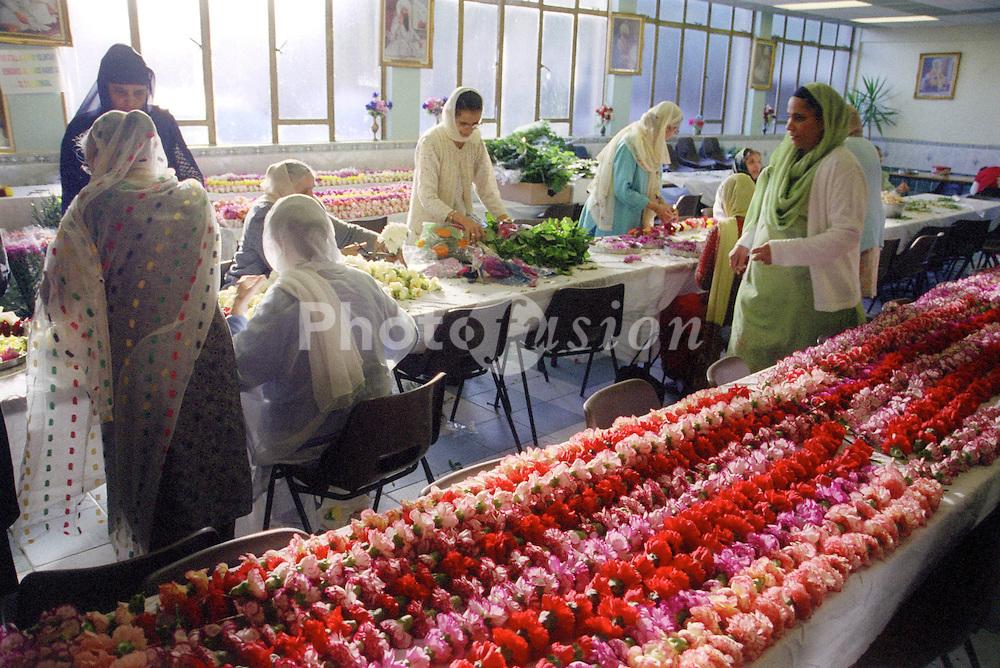 Asian women making garlands for the Baisakhi festival,