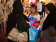 06 JULY 2011 - BANGKOK, THAILAND: A Thai souvenir vendor sells novelties to Middle Eastern women in the Soi Arab section of Bangkok. Soi Arab is an alleyway in Bangkok. What started as an alley has now grown into a neighborhood that encompasses several blocks of restaurants, hotels and money exchanges that cater to Middle Eastern visitors to Thailand. The official name of the street is Sukhumvit Soi 3/1, located in North Nana between Sukhumvit Soi 3 and Sukhumvit Soi 5, not far from the Nana Plaza night-life area and the Grace Hotel popular among Arabs.   PHOTO BY JACK KURTZ