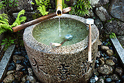 Water source for purification of believers at temple entrance in Kyoto, Japan