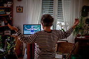 A 77 year old pensioner is practising Yoga in social distance via television instructions at home.