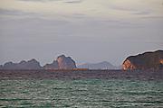 Thailand, Ko Kradan. Sunset. Barges passing Ko Muk (r.)