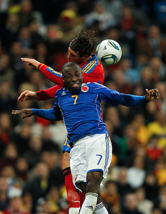 Spain's Sergio Ramos, top, vies for the ball with Colombia's Pablo Armero, bottom, during an international friendly soccer match at the Santiago Bernabeu stadium in Madrid on Wednesday, Feb. 9, 2011. .