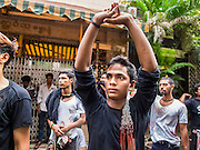 04 NOVEMBER 2014 - YANGON, MYANMAR: Burmese men pray during a break in flagellation ceremony on Ashura in Yangon. The flagellation shows solidarity with Hussein and his family. Mogul Mosque is the principal Shia mosque in Yangon. Ashura commemorates the death of Hussein ibn Ali, the grandson of the Prophet Muhammed, in the 7th century. Hussein ibn Ali is considered by Shia Muslims to be the third imam and the rightful successor of Muhammed. He was killed at the Battle of Karbala in 610 CE on the 10th day of Muharram, the first month of the Islamic calendar. According to Myanmar government statistics, only about 4% of the population is Muslim. Many Muslims have fled Myanmar in recent years because of violence directed against Burmese Muslims by Buddhist nationalists.     PHOTO BY JACK KURTZ