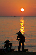Phu Quoc Island. Long Beach (Bai Truong). Women with cone hats at sunset.