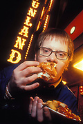 Fast Food, Man eating Fish and Chips at night outside Funland, UK 2000s