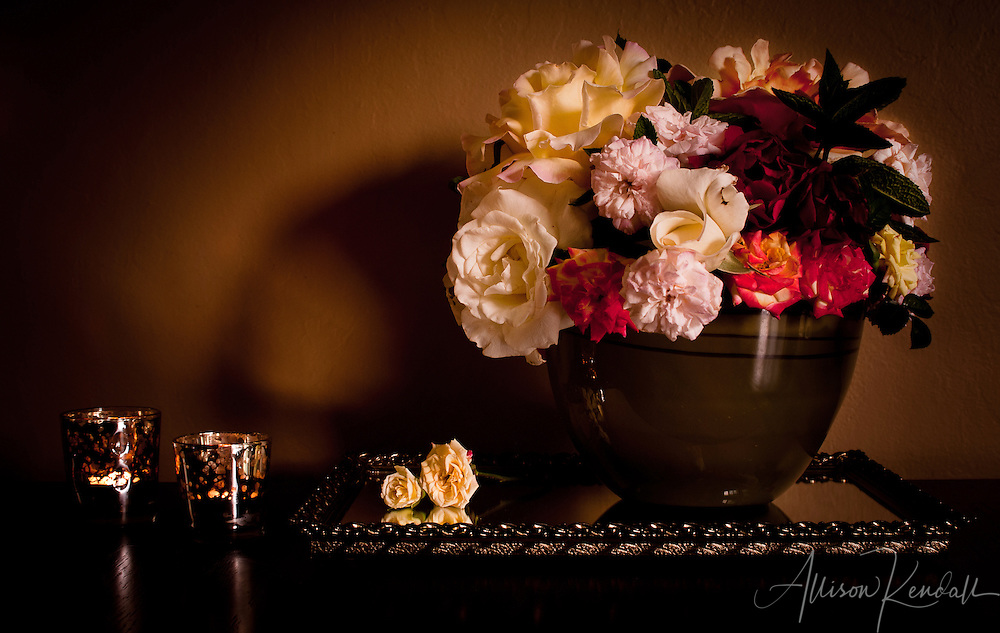A bowl of garden roses and two candles in the soft glow and shadows of a quiet room.