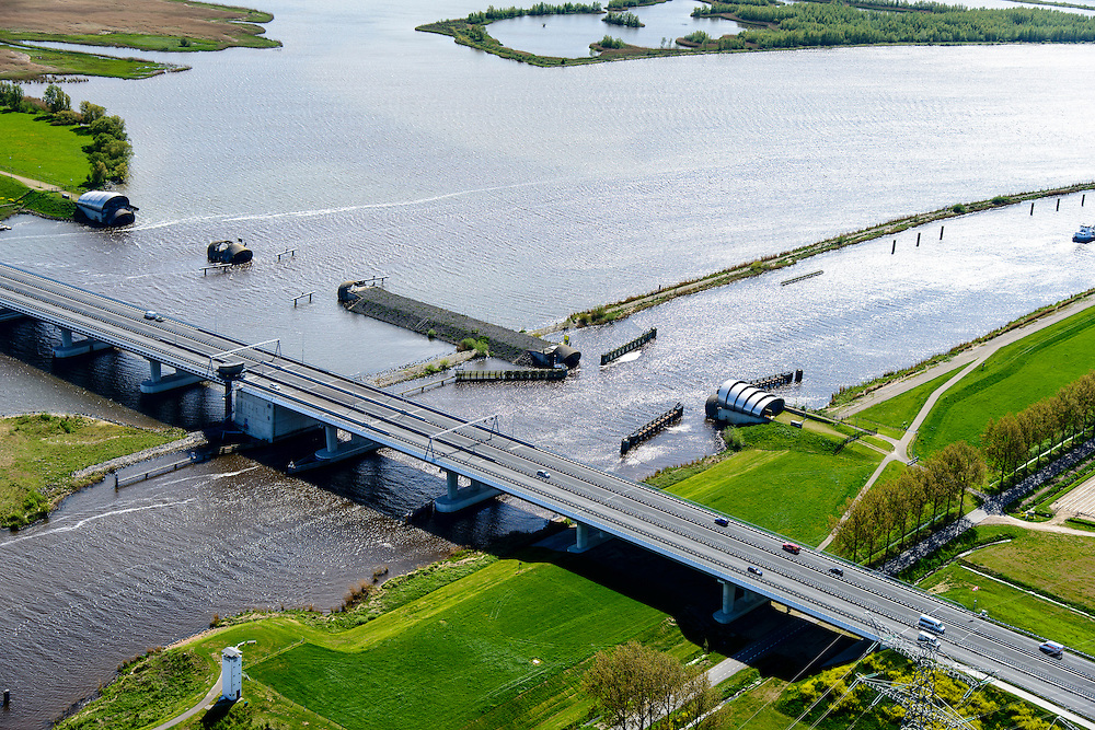 Nederland, Flevoland, Overijssel, Noordoostpolder, 07-05-2015. Ramspolbrug met N50, over de vaargeul het Ramsdiep. Naast de brug de balgstuw, onderdeel van Waterkering Kampen, tussen Ketelmeer en Zwarte Water (voorgeond). De balgstuw is een stormvloedkering en bestaat uit een opblaasbare dam of dijk, opgebouwd uit drie balgen. In niet-opgeblazen toestand liggen de balgen op de bodem. De witte betonenn toren in de voorgrond is  een voormalige luchtwachttoren.<br /> Ramspol bridge and Ramspol barrier, inflatable dike, between Ketelmeer and Black Water. The Balgstuw (bellow barrier) is a storm barrier and consists of an inflatable dam or dyke, composed of three bellows. Usually, each bellow rests on the bottom of the water<br /> luchtfoto (toeslag op standard tarieven);<br /> aerial photo (additional fee required);<br /> copyright foto/photo Siebe Swart