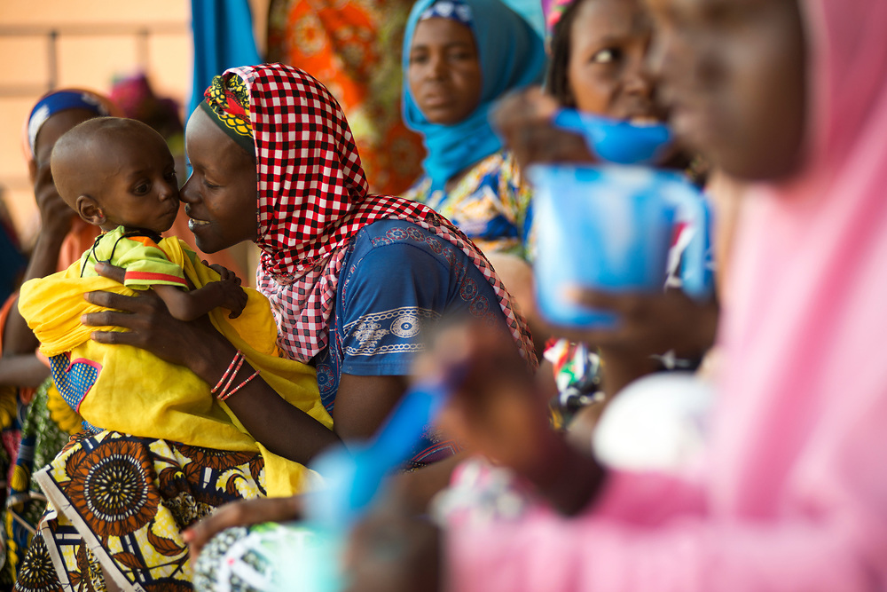 Mothers and children eating a meal at the Save The Children malnutrition clinic at the Aguie hospital in the Maradi region of southern Niger. Suffering from malnutrition themselves, mothers are often unable to breast feed which in turn causes malnutrition among their children. Located in the Western Sahel, the landlocked country suffers from chronic malnutrition and food insecurity caused by climate related drought and erratic rainy seasons, inadequate arable land, one of the highest demographic growth rates in the world, poor social and sanitary living conditions and widespread poverty. Food insecurity affects children under five and women disproportionately, especially in rural areas. Aguie, Niger. 15/07/2017.
