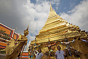 Wat Phra Keo and Grand Palace. Staues of mythical beings. Tourists taking souvenir photos.