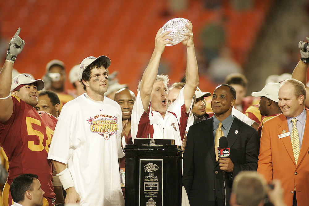 University of Southern California head coach Pete Carroll hold up the ADT championship trophy as linebacker Lofa Tatupu, quarterback Matt Leinart , and USC alumnus Lynn Swann look on after USC's 55-19 victory over Oklahoma on January 4, 2005 in the FedEx Orange Bowl at Pro Player Stadium in Miami, Florida.