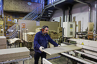 SOVERIA MANNELLI, ITALY - 16 NOVEMBER 2016: Beechwood is cut here by a worker in the warehouse of Camillo Sirianni, a school furniture manifacturer in Soveria Mannelli, Italy, on November 16th 2016.<br /> <br /> Camillo Sirianni is a third generation family business that started as a family mechanized carpentry in 1909 and transformed into a leading school furniture manufacturer. In a high-tech warehouse in the outskirts of Soveria Mannelli, they assemble thousands of Calabrian beechwooden, colorful desks, benches, closets and other accessories that are later shipped to many corners of the globe, from the United Kingdom to the Emirates, from central America to Polynesia.<br /> <br /> Soveria Mannelli is a mountain-top village in the southern region of Calabria that counts 3,070 inhabitants. The town was a strategic outpost until the 1970s, when the main artery road from Naples area to Italy's south-western tip, Reggio Calabria went through the town. But once the government started building a motorway miles away, it was cut out from the fastest communications and from the most ambitious plans to develop Italy's South. Instead of despairing, residents benefited of the geographical disadvantage to keep away the mafia infiltrations, and started creating solid businesses thanks to its administrative stability, its forward-thinking mayors and a vibrant entrepreneurship numbering a national, medium-sized publishing house, a leading school furniture manufacturer and an ancient woolen mill.