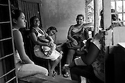 Sisters Laura and Deyanira sit on the porch and joke with a cousin. Nicaraguan families tend to be very large and very close. Laura and her son Israel can count the number of cousins they have living in Tejarcillos and other barios of San Jose.