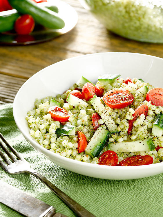 A healthy salad made with Isaeili Couscous and broccoli pesto, with cherry tomatoes and English Cucumber.