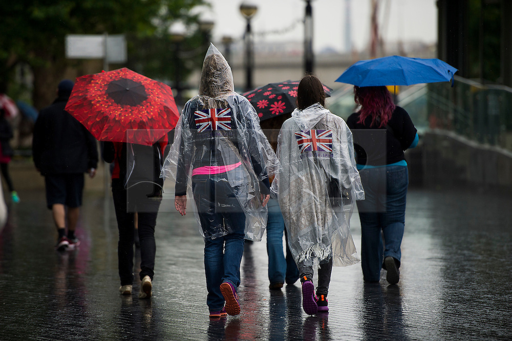 © Licensed to London News Pictures. 29/05/2015. London, UK. Members of the public wearing rain coat ponchos in the rain in front of Tower Bridge in central London on a wet and rainy morning.. Photo credit: Ben Cawthra/LNP