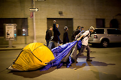 Tue Nov 15, 2011: A member of the Occupy Wall Street camp drags his tent away from Zuccotti Park after an early hours NYPD raid cleared the makeshift camp. Sanitation crews took custody of some personal property and discarded large piles of a wide array of supplies. Arrest estimates - at time of filing - are in the neighborhood of 200. Credit: Rob Bennett for The Wall Street Journal