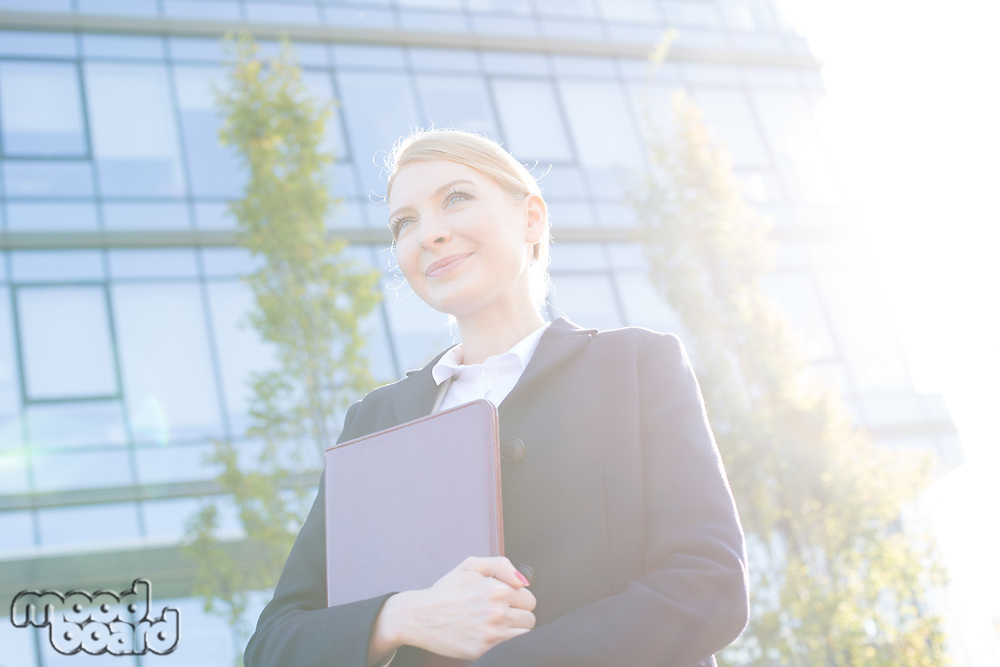 Low angle view of thoughtful businesswoman holding folder on sunny day