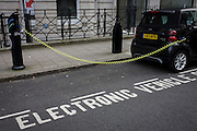 A parked Smart car recharges electric power at an EDF charging point in central London.