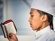 10 JULY 2015 - BANGKOK, THAILAND: A boy reads a pocket version of the holy Q'uran (Koran) before Iftar at Haroon Mosque in Bangkok. Iftar is the evening meal when Muslims end their daily Ramadan fast at sunset. Iftar is a communal event at Haroon Mosque and hundreds of people usually attend the meal.     PHOTO BY JACK KURTZ