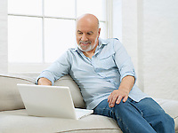 Middle-aged man sitting on sofa using laptop
