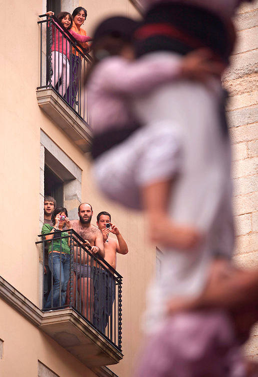 """IMAGE SALES CONTACT/IMATGE A LA VENDA CONTACTAR tonivilches@tonivilches.com o 629 300 963..October, 25th, 2009. HUMAN TOWERS MEETING IN SANT NARCIS FESTIVITIES IN GIRONA CITY CATALUNYA CATALONIA.SPAIN..""""Castells"""" -is a Catalonian word that means castles- they are a cultural phenomenon particular to Catalonia and consist of erecting human towers. This tradition originated at the end of the 18th century in Valls, Tarragona, when rival groups of people called """"colles"""", began to compete in constructing the different kinds of human towers that we recognise nowadays. There are three definite parts to a castle; the """"pinya"""" or base the """"tronc"""" or trunk and the """"pom de dalt"""" or the crown of the castle. The """"pinya"""" is the horizontal base of the construction on which all the accumulated weight rests and is used to stabilise and strengthen the erected structure, as well as softening or breaking the falls if any should occur. The vertical structure perpendicular to the pinya is the trunk and consists of a certain number of people on each storey, varying from 1 to 9 people depending on the castle and this also gives us the name of the castle. At the very top of the castle are the """"canalla"""" or """"anxaneta"""", and they make up the """"pom de dalt"""", the crown of the castle, and because they are more agile and light-footed they are the ones in charge of climbing to the very top. One or two supporting structures can be built on top of the """"pinya"""" if the castle is very high. The one directly on top of the pinya is called the """"folre"""" and the one on top of that is the """"manilles"""". So the folre is at second level and the manilles at third level height with respect to the ground. Every person who takes part in the building is called a """"casteller"""" -castle-maker""""."""