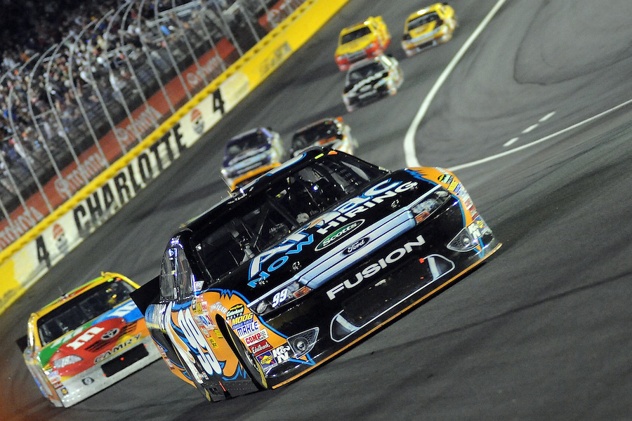 Sprint Cup Series driver Carl Edwards (99) leads the pack out of turn four during the final segment of the Sprint Cup All-Star Race at Charlotte Motor Speedway in Concord, NC. Sprint Cup Series driver Carl Edwards captured the race over Sprint Cup Series driver Kyle Busch.
