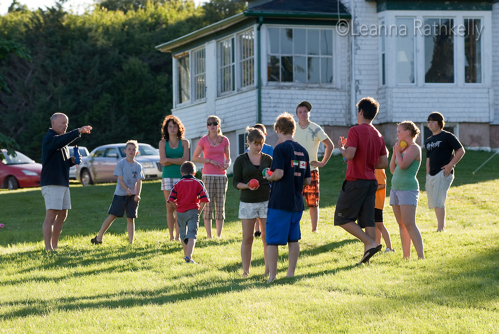 Kids play a game of bocce on the lawn outside an old farm house on Prince Edward Island, Canada.