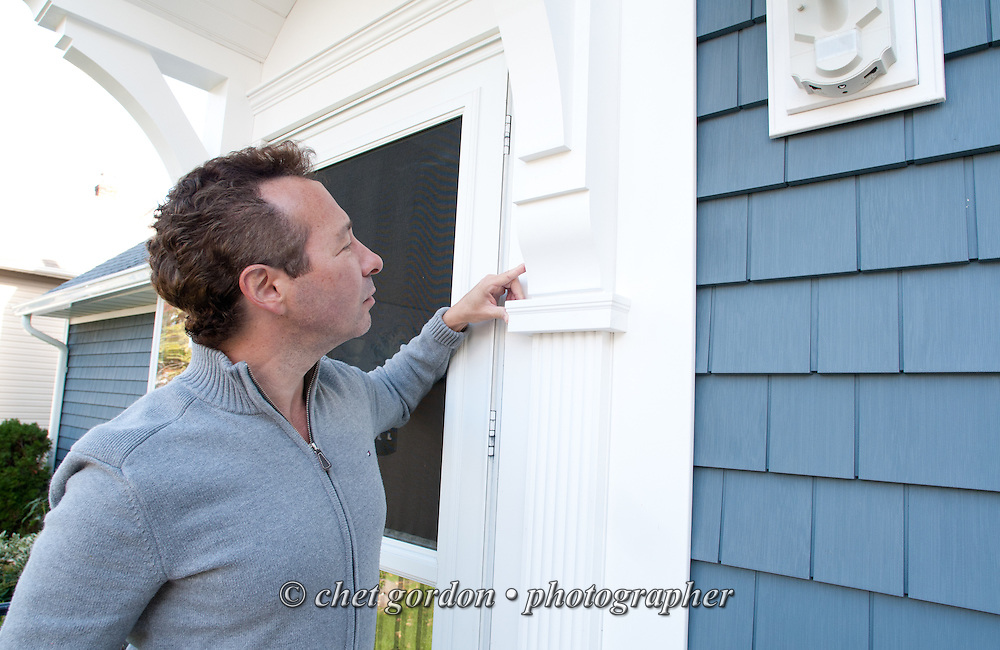 Craig Furer examines the new front door molding of his Cranford, NJ home on Sunday, October 23, 2016. Furer and his wife Jen hired Magnolia Home Remodeling Group to complete a full exterior makeover. The company replaced the siding with shake and clapboard, added various architectural accents, replaced the roof, modified the roofline, built a front portico and replaced two windows. Craig spent a lot of time researching this project before it began and is thrilled with the overall result.  © Chet Gordon for Angie's List