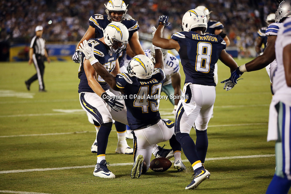 San Diego Chargers running back Branden Oliver (43) is surrounded by happy teammates as he waves his arms in celebration after scoring a touchdown on a 10 yard run late in the second quarter that gives the Chargers a 14-7 lead during the 2015 NFL preseason football game against the Dallas Cowboys on Thursday, Aug. 13, 2015 in San Diego. The Chargers won the game 17-7. (©Paul Anthony Spinelli)
