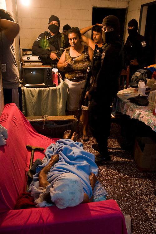 Police search an apartment for a member of MS-13 while a sick women lies on a couch in the impoverished Parieso Barrio in San Salvador.  El Salvador has given up many civil rights in the name of pursuing gangs. Human rights groups say the violations which mostly impact the poor, only increase motivation to join gangs.