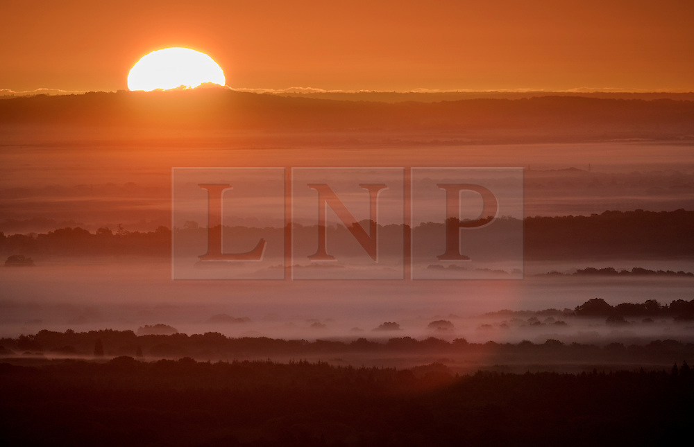 © Licensed to London News Pictures. 03/10/2016. Dorking, UK. The sun rises over the mist filled hills and valleys of Surrey and West Sussex. Sunshine and warm autumn weather are forecast for today. Photo credit: Peter Macdiarmid/LNP