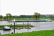 Nederland,  13-4-2018 Een binnenvaartschip vaart over de Maas richting Rotterdam. Het passeert een kleine jachthaven .Foto: Flip Franssen