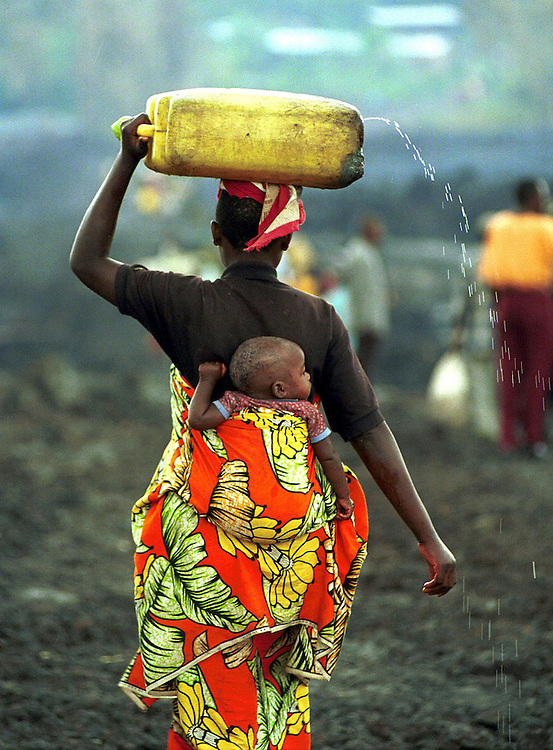 A woman from the rural Bugarura district of Goma carries her child and a leaking water holder across the lava towards the centre of the destroyed city of Goma, Democratic republic of Congo. Goma, a city of 400,000 people was totally destroyed when it was engulfed in lava from the Nyiragongo volcano which erupted on 17/1/02.