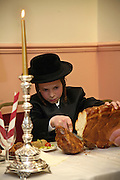 A 13 year-old Orthodox Jewish boy cuts the bread for everyone at his Bar Mitzvah meal. The Bar Mitzvah signals the coming of age for a young Jewish boy, they become responsible to observe the commandments of the Torah. It coincides with physical puberty and they begin to participate in all areas of Jewish life. A Bar mitzvah ceremony is a big occasion, the young boy reads a section from the Torah to his family and friends and a mitzvah meal is consumed.
