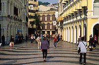 People walking in front of the colorful colonial buildings in the Largo de Senado, Macau, China.