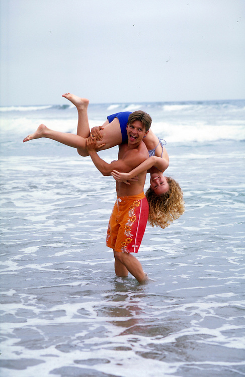 Lifestyle picture of young couple playing in the surf in Carlsbad, CA