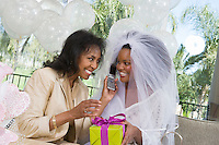 Bride using mobile phone with mother at bridal shower