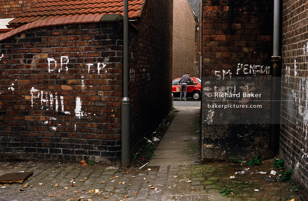 Through a filthy alleyway in Toxteth, Liverpool a local man still washes his car amid socially-deprived streets and housing