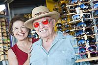 Portrait of senior couple trying on sunglasses, smiling