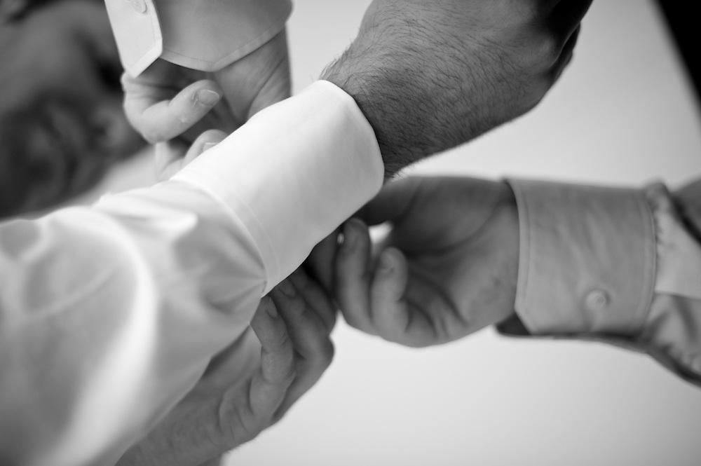 Der Vater des Bräutigams hilft beim zuknöpfen des Hemdes