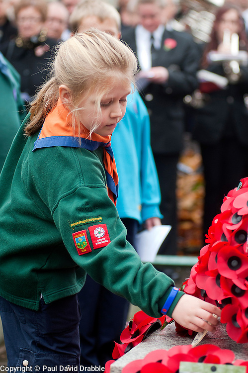 A Cub scout from the 82nd Sheffield (Chapeltown) leaves a simple wooden cross and poppy at the local War Memorial in Chapeltown Park Sheffield South Yorkshire, during a local Remembrance Day service on Sunday.13 November 2011. Image © Paul David Drabble