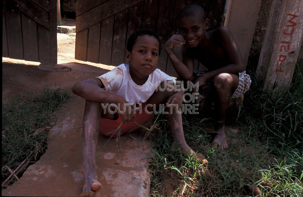 Two little boys sitting on the muddy ground, Brazil, 2000's
