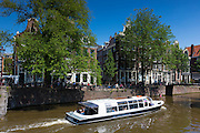 Tour group sightseeing on tourist cruise boat by Brouwersgracht and Herengracht canal, Jordaan district, Amsterdam, Holland
