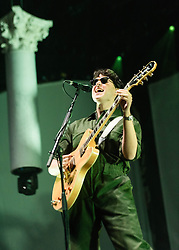 © Licensed to London News Pictures. 13/11/2013. London, UK.   Vampire Weekend performing live at The O2 Arena. In this picture - Ezra Koenig.  Vampire Weekend is an American rock band from New York City consisting of members Ezra Koenig (lead vocals, guitar), Rostam Batmanglij (producer, keyboards, guitar, backing vocals), Chris Tomson (drums)<br /> Chris Baio (bass,vocals). Photo credit : Richard Isaac/LNP