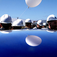 A balloon and hardhat clad employees of the Ocean Honda dealership are reflected on the roof of a new car as workers and guests tour the dealership's new showroom and shop under construction in Soquel, California on Wednesday September 17, 2008.