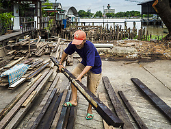 August 16, 2017 - Bangkok, Thailand - A man scavenges used construction wood left behind after city officials tore down several homes built on pilings in the Wat Thewarat Kunchorn community along the Chao Phraya River in Bangkok. City officials are evicting people who live in small homes along the riverfront so they can build a 14km long promenade. Their plans call for removal of 273 homes in 14 riverside communities. The people who live in the homes are among the most impoverished in Bangkok. (Credit Image: © Sean Edison via ZUMA Wire)