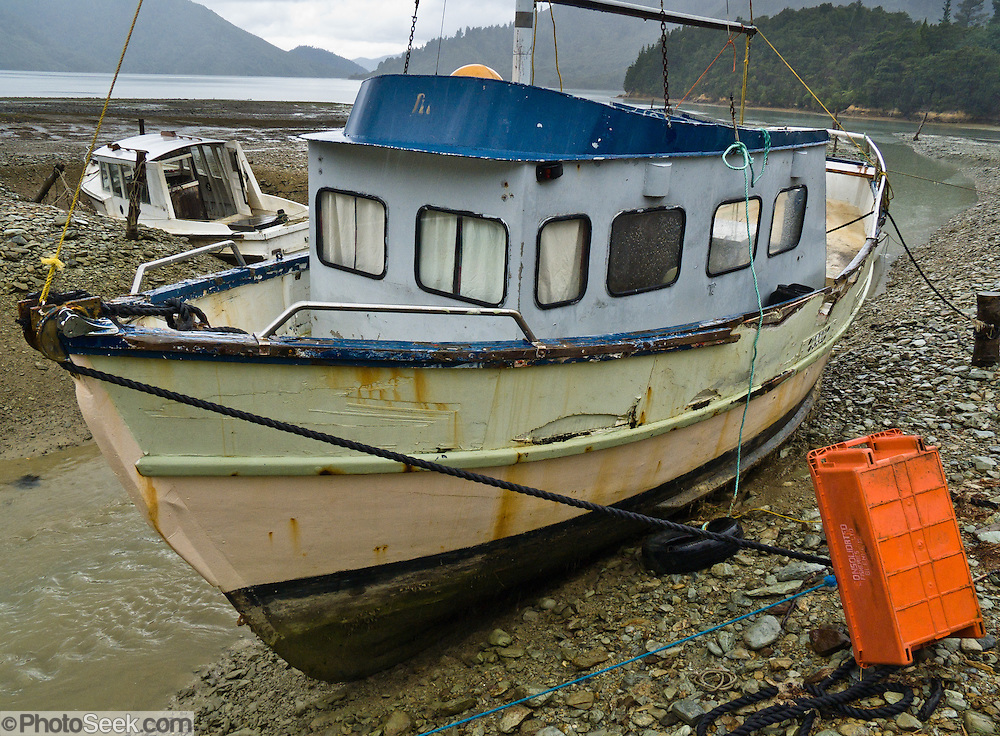 Boats stranded by low tide on Nydia Bay. Nydia Track, South Island, New Zealand
