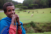 A portrait of a young boy who is out looking after his familys cattle by a river in Ethiopia. He is wearing a really colourful blue blanket.