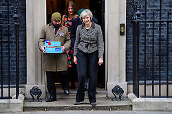 ©  London News Pictures. 31/10/2016. London, UK. British prime minister THERESA MAY meets veterans involved in the Royal British Legion on the steps of 10 Downing Street to donate to the Poppy Appeal. The Poppy Appeal raises funds for the armed forces  by selling red poppies that are worn around remembrance Sunday, to remember fallen Service men and women killed in conflict. Photo credit: Ben Cawthra/LNP
